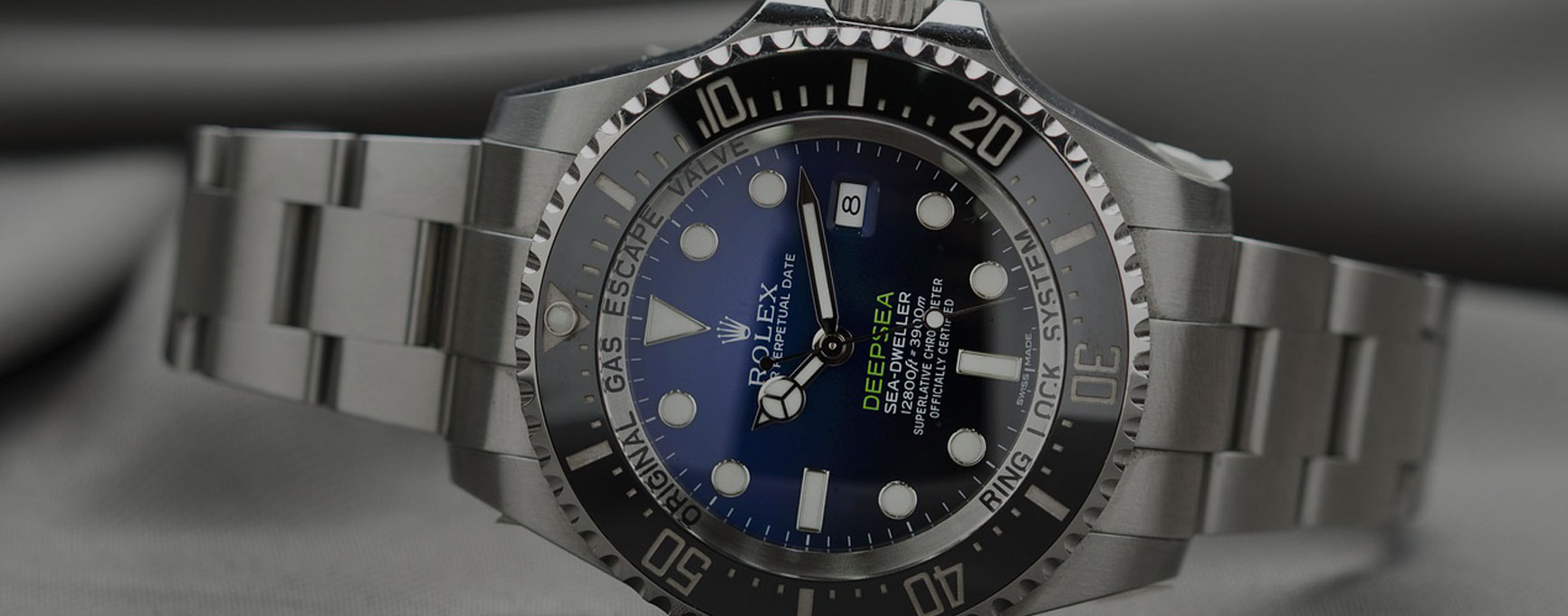 Silver exterior rolex watch with blue interior design and minimal green accents